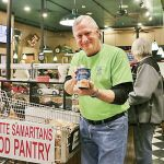 FPC member Lamar Hasty collects food donations for Fayette Samaritans at December's benefit. Photo/Special.