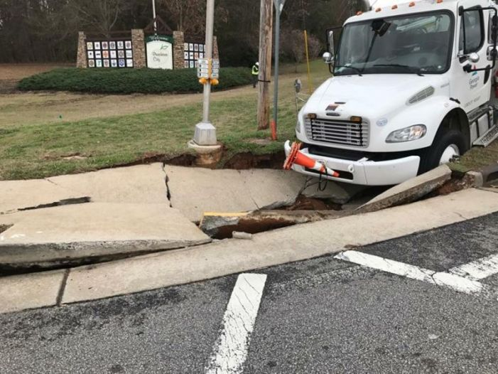 Sinkhole traps utility truck at busy PTC intersection