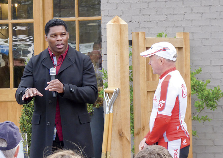 University of Georgia football legend Herschel Walker, left, speaks with Pinewood Forest Chief Visionary Dan Cathy and the large group of people attending the March 16 groundbreaking for the Piedmont Wellness Center located at Pinewood Forest in Fayetteville. Photo/Ben Nelms.