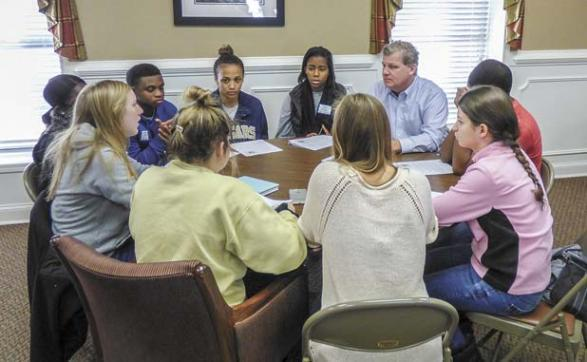 Nearly 50 teens from AVPRIDE got a look at how local government works in a Dec. 10 meeting with administrators at the old courthouse in Fayetteville. Fayette County Administrator Steve Rapson (in blue shirt, top right) listens to a student's question during a small group session. Photo/Ben Nelms.